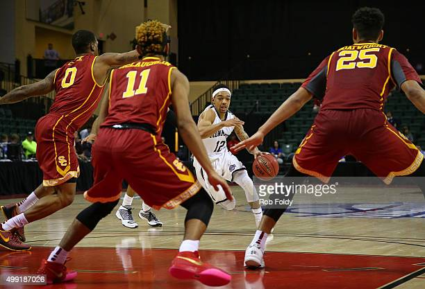 Justin Robinson of the Monmouth Hawks drives to the basket as Darion Clark Jordan McLaughlin and Bennie Boatwright of the USC Trojans defend during...