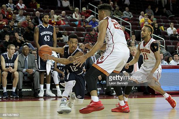Justin Robinson of the Monmouth Hawks handles the ball against Bennie Boatwright of the USC Trojans at Galen Center on November 16 2015 in Los...