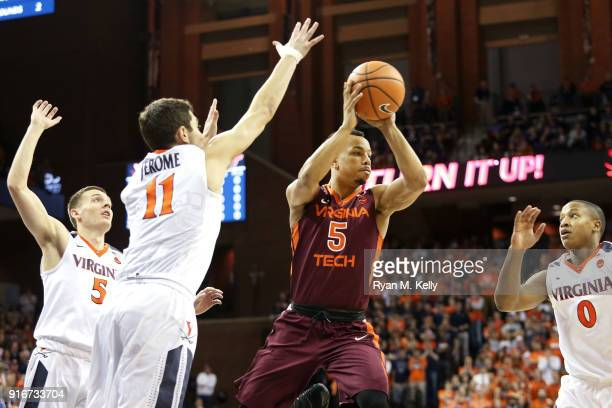 Justin Robinson of the Virginia Tech Hokies looks to pass between Kyle Guy Ty Jerome and Devon Hall of the Virginia Cavaliers in the first half...