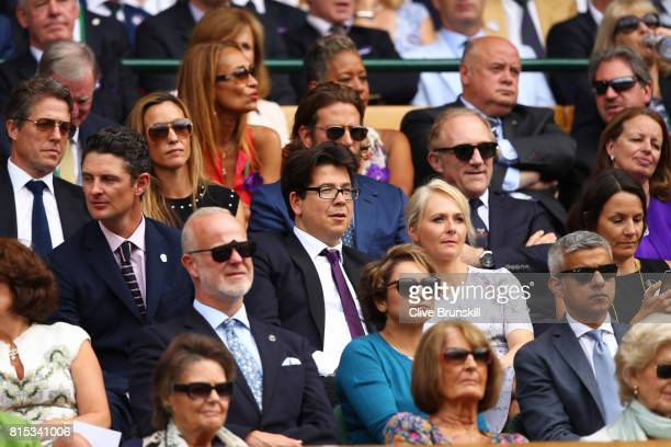 Justin Rose Hugh Grant and Michael McIntyre look on the centre court royal box prior to the Gentlemen's Singles final between Roger Federer of...