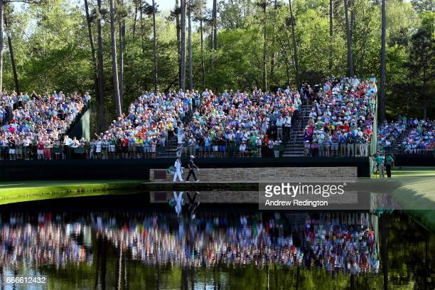 Justin Rose of England and caddie Mark Fulcher cross the Sarazen Bridge on the 15th hole during the final round of the 2017 Masters Tournament at...
