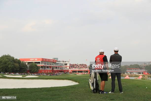 Justin Rose of England and caddie Mark Fulcher prepares to play a shot on the 18th hole during the final round of the WGC HSBC Champions at Sheshan...