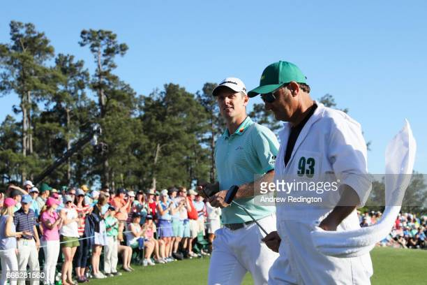 Justin Rose of England and caddie Mark Fulcher smile as they walk off the 18th green during the third round of the 2017 Masters Tournament at Augusta...