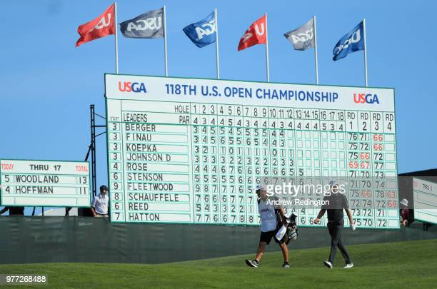 Justin Rose of England and caddie Mark Fulcher walk in front of a leaderboard on the 14th green during the final round of the 2018 US Open at...