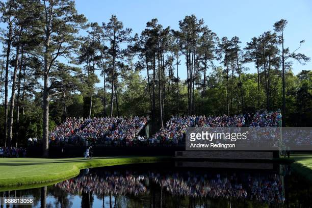 Justin Rose of England and caddie Mark Fulcher walk to the Sarazen Bridge on the 15th hole during the final round of the 2017 Masters Tournament at...