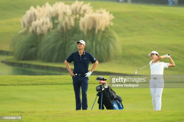 Justin Rose of England and junior golfer Zhai Mindy Ximiao play during practice rounds prior to the WGC HSBC Champions at Sheshan International Golf...