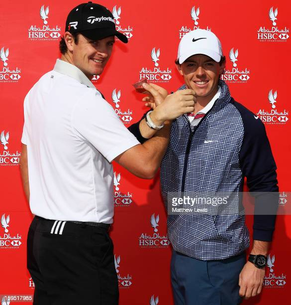 Justin Rose of England and Rory McIlroy of Northern Ireland drink coffee during a photocall ahead of the Abu Dhabi HSBC Golf Championship at Abu...