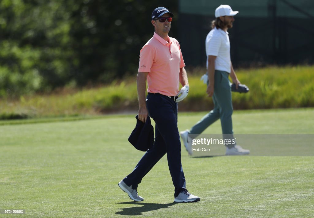 Justin Rose (L) of England and Tommy Fleetwood (R) of England walk on the second green during a practice round prior to the 2018 U.S. Open at Shinnecock Hills Golf Club on June 12, 2018 in Southampton, New York.