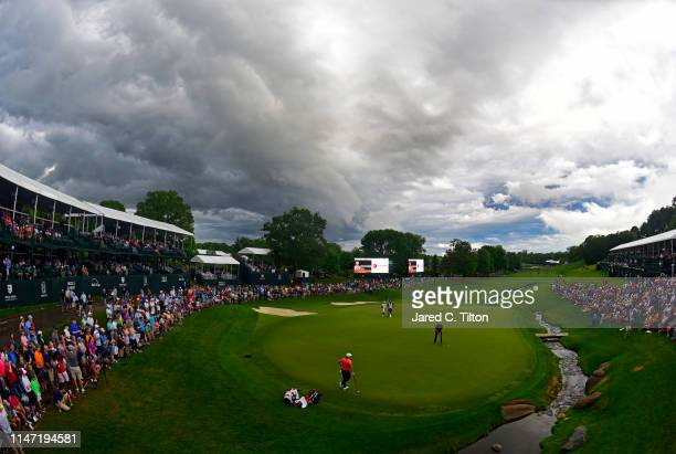 Justin Rose of England attempts a putt on the 18th green as Rory McIlroy of Northern Ireland looks on during the final round of the 2019 Wells Fargo...