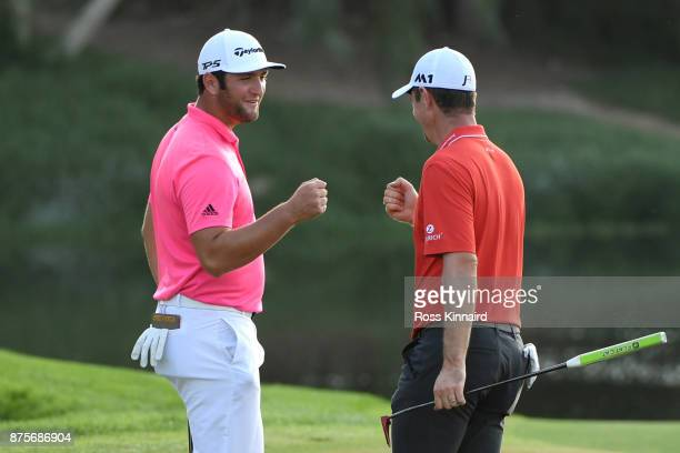 Justin Rose of England celebrates a birdie on the 16th green with Jon Rahm of Spain during the third round of the DP World Tour Championship at...