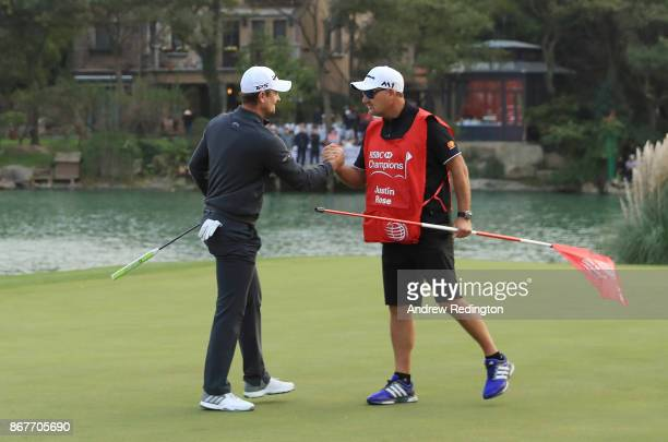 Justin Rose of England celebrates with his caddie Mark Fulcher on the 18th green after finishing 14 under during the final round of the WGC HSBC...