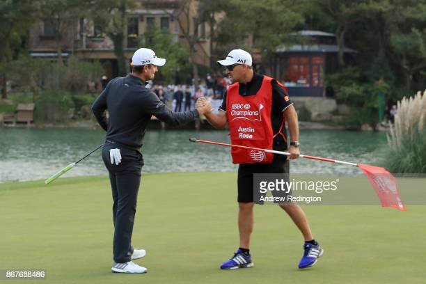Justin Rose of England celebrates with Mark Fulcher on the 18th green after finishing 14 under during the final round of the WGC HSBC Champions at...