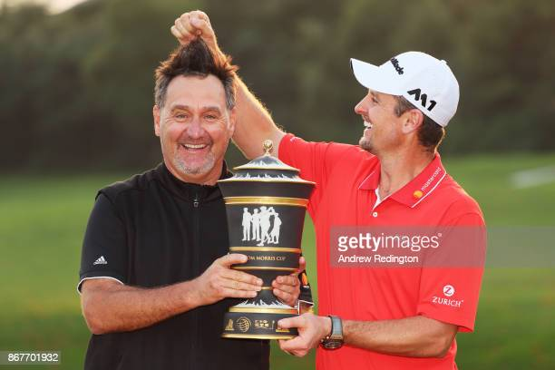 Justin Rose of England celebrates with the Old Tom Morris Cup and caddie Mark Fulcher after finishing 14 under to win the WGC HSBC Champions at...