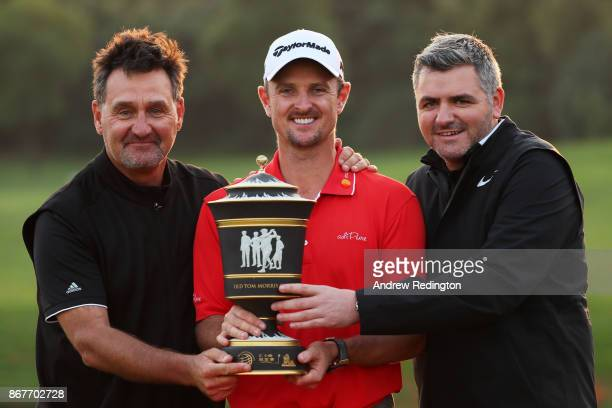 Justin Rose of England celebrates with the Old Tom Morris Cup and caddie Mark Fulcher and agent Paul McDonnell after finishing 14 under to win the...
