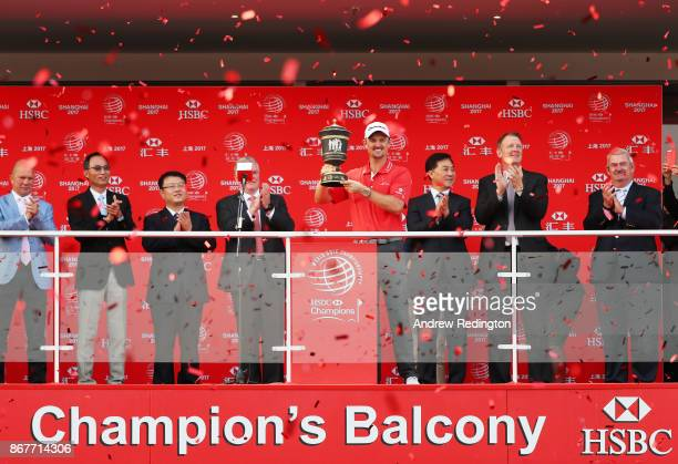 Justin Rose of England celebrates with the Old Tom Morris Cup on the Champion's Balcony after finishing 14 under to win the WGC HSBC Champions at...