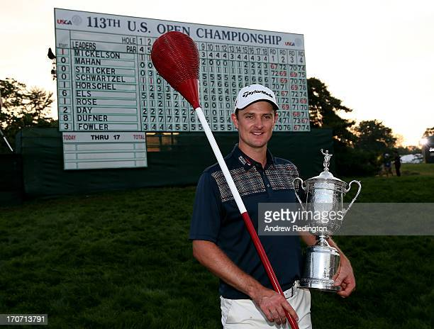 Justin Rose of England celebrates with the U.S. Open trophy while holding a wicker basket flagstick after winning the 113th U.S. Open at Merion Golf...