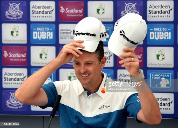 Justin Rose of England changes hats as he speaks to the media during previews for the Aberdeen Standard Investments Scottish Open at Gullane Golf...