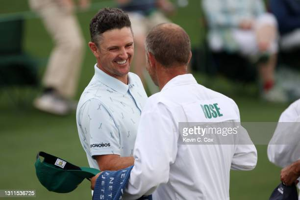 Justin Rose of England fist bumps his caddie, David Clark, after his round on the 18th green during the first round of the Masters at Augusta...