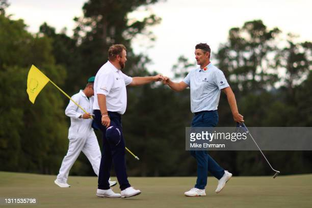 Justin Rose of England fist bumps Shane Lowry of Ireland on the 18th green during the first round of the Masters at Augusta National Golf Club on...