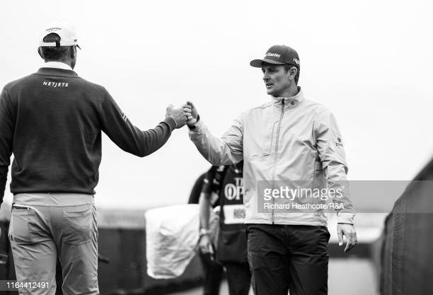 Justin Rose of England greets Matt Kuchar of the USA during the final round of the 148th Open Championship held on the Dunluce Links at Royal...
