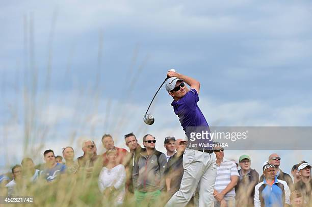 Justin Rose of England hits his tee shot on the second hole as a gallery of fans look on during the second round of The 143rd Open Championship at...