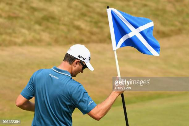 Justin Rose of England holds the pin flag on hole one during day four of the Aberdeen Standard Investments Scottish Open at Gullane Golf Course on...