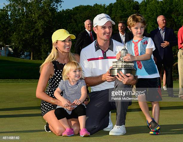 Justin Rose of England holds the trophy and poses with his wife Kate and children Charlotte and Leo after winning the Quicken Loans National at...