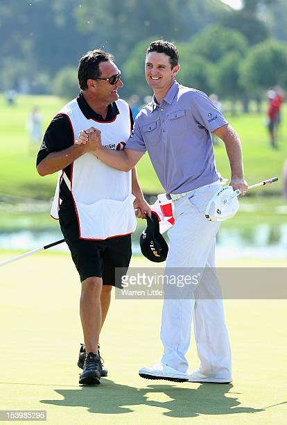 Justin Rose of England is congratulated by his caddie Mark Fulcher after beating fellow countryman Lee Westwood to win the Turkish Airlines World...