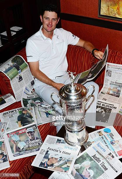 Justin Rose of England is surrounded by the morning papers as he reads the stories of his US Open win at Merion Golf Club at his hotel on June 17,...