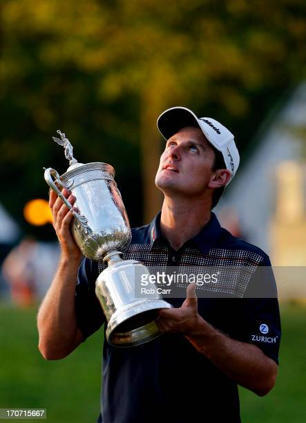 Justin Rose of England looks up as he celebrates with the US Open trophy after winning the 113th US Open at Merion Golf Club on June 16 2013 in...