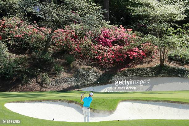 Justin Rose of England plays a shot from a bunker on the 12th hole during a practice round prior to the start of the 2018 Masters Tournament at...