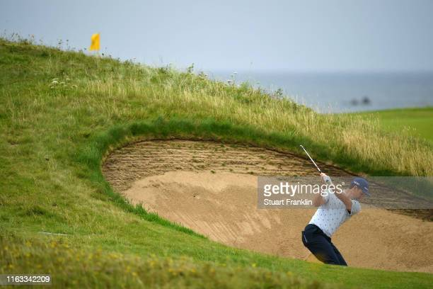 Justin Rose of England plays a shot from a bunker on the fifth hole during the final round of the 148th Open Championship held on the Dunluce Links...