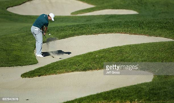 Justin Rose of England plays his shot out of the bunker on the 17th hole during the third round of the Farmers Insurance Open at Torrey Pines South...
