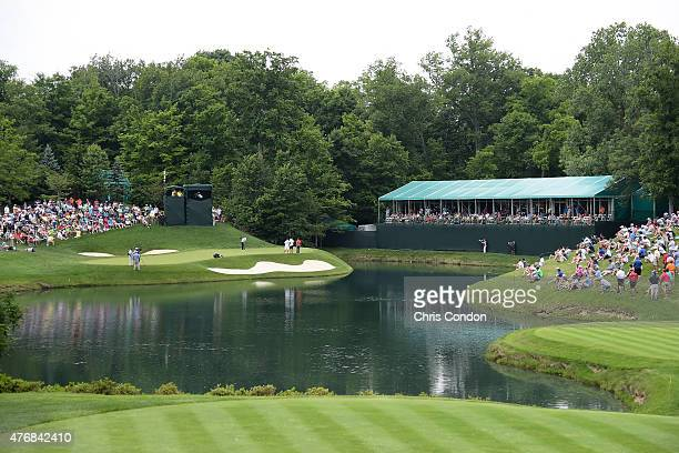 Justin Rose of England putts on thew 12th green as Francesco Molinari of Italy looks on during the final round of the the Memorial Tournament...