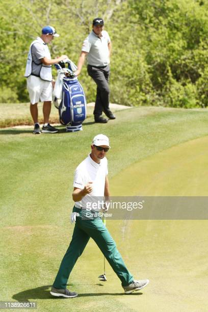 Justin Rose of England reacts to his birdie on the 17th green as Eddie Pepperell of England looks on during the second round of the World Golf...