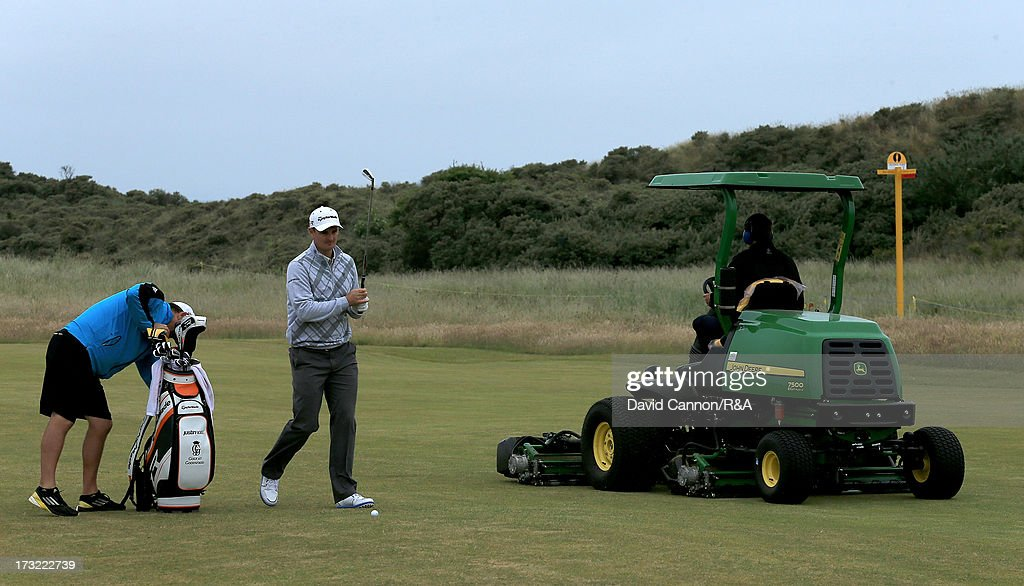 Justin Rose of England, the 2013 US Open Champion, escapes the close attention of a fairway mower preparing the course during a practice round as a preview for the 2013 Open Championship at Muirfield on July 10, 2013 in Gullane, Scotland.