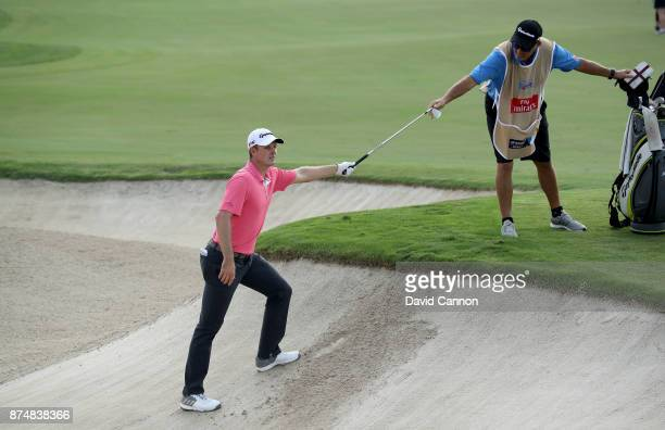 Justin Rose of England uses his caddie Mark Fulcher to leave the deep bunker after his second shot on the third hole during the first round of the DP...