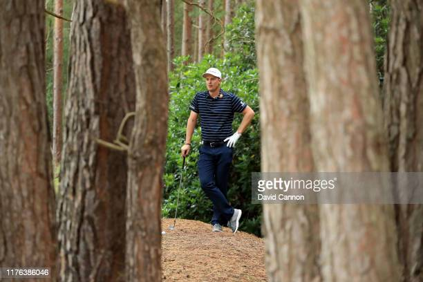 Justin Rose of England waits to play his third shot from the trees on the 13th hole during the final round of the BMW PGA Championship on the West...