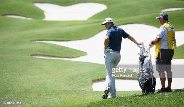 Justin Rose of England waits with caddie Mark Fulcher to play a shot on the seventh hole during the third round of the 2018 PGA Championship at...