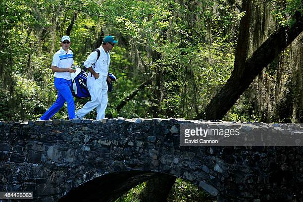 Justin Rose of England walks across the Nelson Bridge with his caddie Mark Fulcher during the third round of the 2014 Masters Tournament at Augusta...