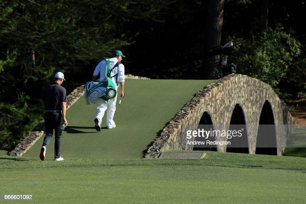 Justin Rose of England walks over the Hogan Bridge with his caddie Mark Fulcher during the final round of the 2017 Masters Tournament at Augusta...