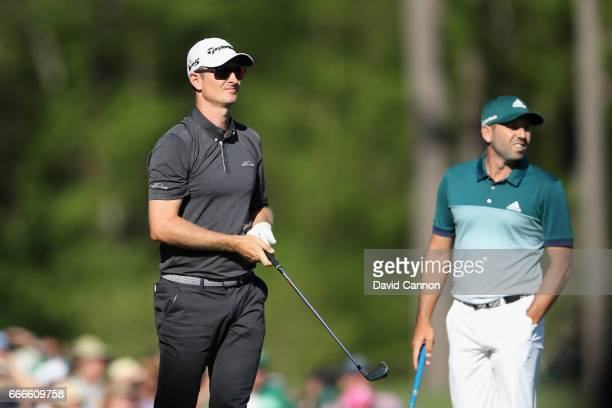Justin Rose of England watches his tee shot on the 12th hole as Sergio Garcia of Spain looks on during the final round of the 2017 Masters Tournament...