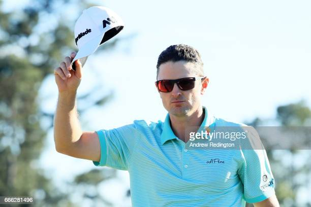 Justin Rose of England waves after making a putt for birdie on the 18th green during the third round of the 2017 Masters Tournament at Augusta...