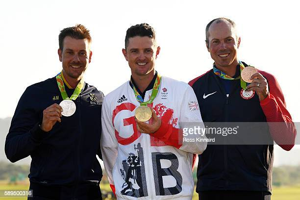 Justin Rose of Great Britain celebrates with the gold medal, Henrik Stenson of Sweden, silver medal, and Matt Kuchar of the United States, bronze...