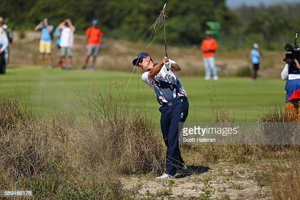 Justin Rose of Great Britain plays from a waste area on the 11th hole during the final round of men's golf on Day 9 of the Rio 2016 Olympic Games at...