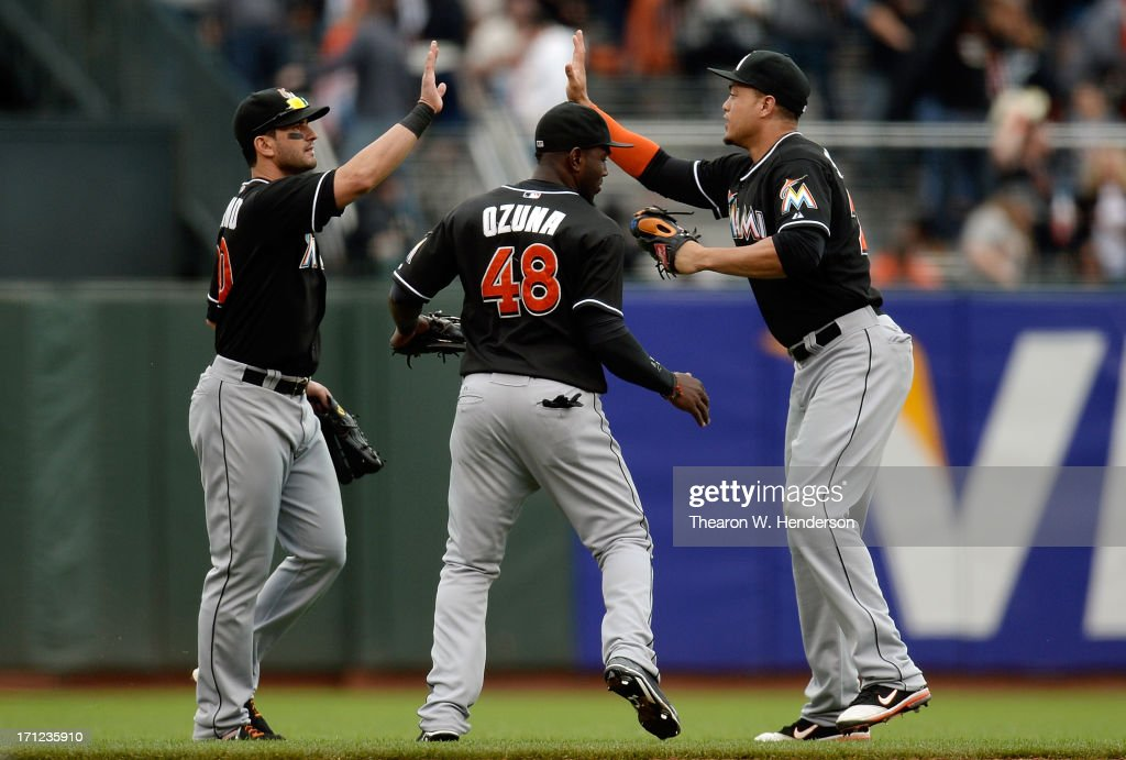 Justin Ruggiano #20, Marcell Ozuna #48 and Giancarlo Stanton #27 of the Miami Marlins celebrate defeating the San Francisco Giants 7-2 at AT&T Park on June 23, 2013 in San Francisco, California.