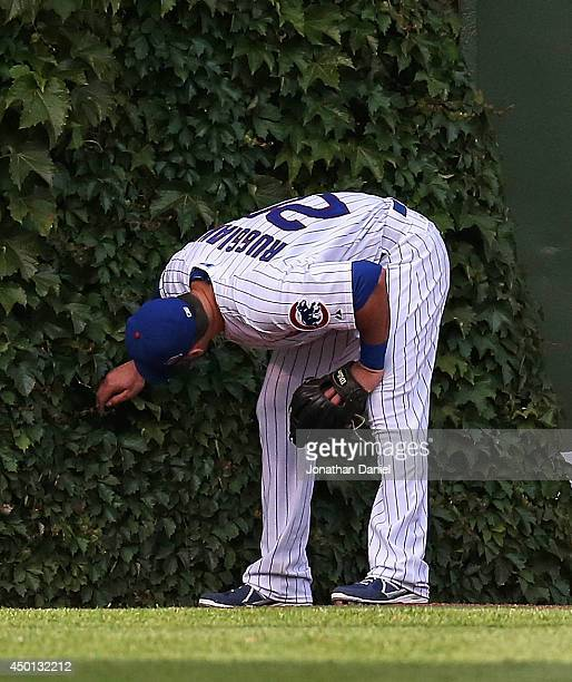 Justin Ruggiano of the Chicago Cubs looks for the ball in the outfield ivy hit for a groundrule double by Jacob deGrom of the New York Mets in the...