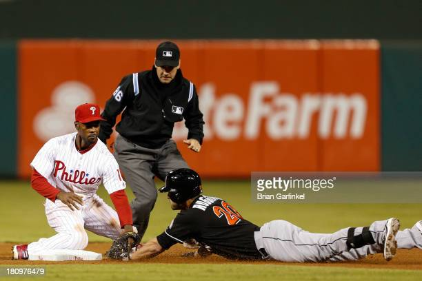 Justin Ruggiano of the Miami Marlins is tagged out at second base by Jimmy Rollins of the Philadelphia Phillies in the fourth inning of the game at...