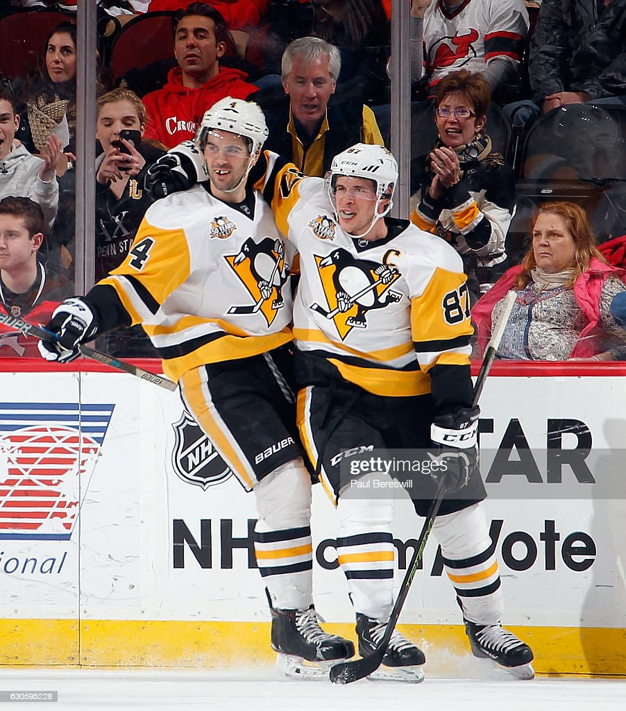 Justin Schultz #4 and Sidney Crosby #87 of the Pittsburgh Penguins celebrate a goal by Schultz in the second period of an NHL hockey game againts the New Jersey Devils at Prudential Center on December 27, 2016 in Newark, New Jersey. Penguins won 5-2.