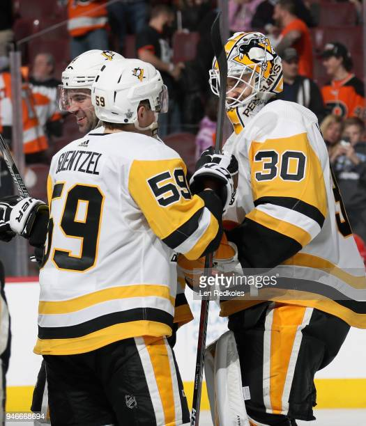 Justin Schultz Jake Guentzel and Matthew Murray of the Pittsburgh Penguins celebrate after defeating the Philadelphia Flyers 51 in Game Three of the...